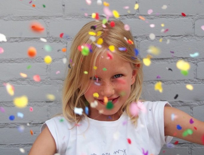 smiling child with rainbow confetti
